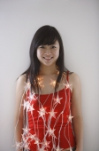 Young woman wearing fairy lights, smiling - Yukmin