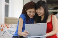 Two teenage girls sitting side by side looking at laptop - Yukmin