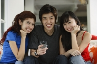 Teenagers sitting side by side, smiling at camera, portrait - Yukmin
