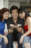 Teenagers sitting side by side, smiling at camera, boy in the middle holding plate with a cake and candle on it - Yukmin