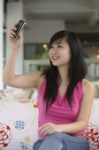 Young woman holding mobile phone, taking a picture of herself - Yukmin