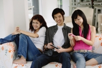 Teenagers sitting side by side, on sofa, listening to music from MP3 players - Yukmin
