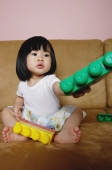 Young girl sitting on sofa, holding toys - Yukmin