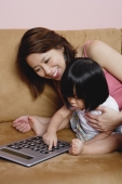 Mother with young daughter, using calculator - Yukmin