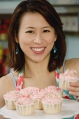 Woman holding plate of cupcakes - Yukmin