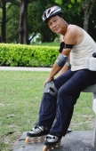 Mature adult with roller blades, sitting in park - Yukmin