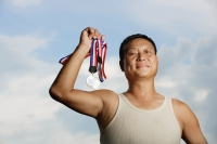 Mature adult in tank top, holding medals - Yukmin