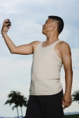 Mature adult in tank top, holding camera, taking pictures of himself - Yukmin