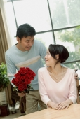 Couple in loving room, man holding bouquet of flowers, woman turning to look at him - blueduck