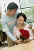 Couple at home, man giving woman bouquet of roses - blueduck