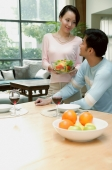 Couple at home, man sitting at dining table, woman standing next to him holding bowl of salad - blueduck