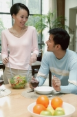 Man sitting at dining table, woman standing next to him tossing a salad - blueduck