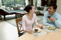 Couple sitting at dining table eating - blueduck