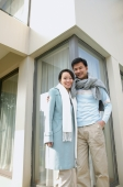 Couple standing outside house, smiling at camera - blueduck