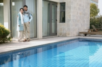 Couple standing outside house, next to swimming pool - blueduck