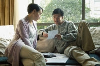 Couple in living room, looking at bills - blueduck