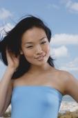 Woman in blue tube top, smiling at camera - Yukmin