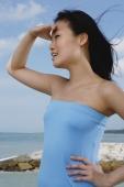 Woman in blue tube top, shielding eyes, looking away - Yukmin