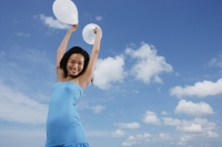 Woman holding balloons in air - Yukmin