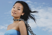 Woman in blue tube top, scarf around her neck, smiling at camera - Yukmin