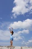 Woman standing on breakwater, holding balloons in air - Yukmin