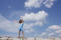 Woman standing on breakwater, waving balloons in air - Yukmin