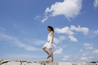 Woman walking on breakwater - Yukmin