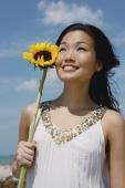 Woman holding sunflower stalk, looking up - Yukmin