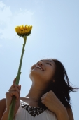 Woman holding sunflower stalk, looking up, low angle view - Yukmin