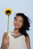 Woman holding sunflower stalk, smiling at camera - Yukmin