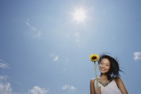 Woman holding sunflower stalk, smiling at camera, low angle view - Yukmin