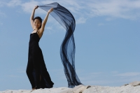 Woman in long black dress, holding scarf in air - Yukmin