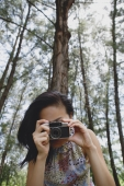 Young woman with camera, taking a picture - Yukmin