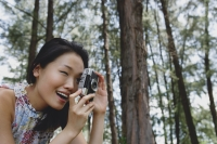 Young woman outdoors, taking a photograph - Yukmin