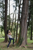 Young woman outdoors, taking a photograph of a tree - Yukmin