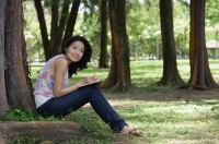 Young woman sitting under a tree, smiling, looking away - Yukmin