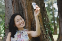 Young woman outdoors, taking a photograph of herself with mobile phone camera - Yukmin