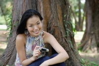 Young woman outdoors, holding a camera, smiling - Yukmin