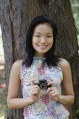 Young woman standing next to tree trunk, holding a camera, smiling - Yukmin