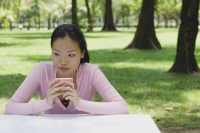 Young woman sitting at outdoor table, holding coffee cup, looking away - Yukmin