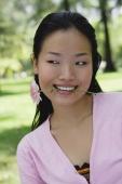 Young woman biting flower stalk, head shot - Yukmin
