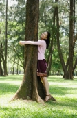 Young woman hugging a tree, smiling - Yukmin