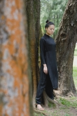 Young woman in traditional Chinese costume, standing amongst trees - Yukmin