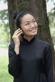 Young woman in traditional Chinese costume, standing next to tree, using mobile phone - Yukmin