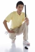 Young man crouching, holding golf club - blueduck