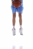 Young man jumping, holding basketball, low section, cropped image - blueduck