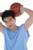 Young man holding basketball behind his head, smiling - blueduck