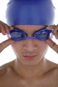 Young man adjusting swimming goggles - blueduck