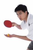 Young man with table tennis paddle and ball, preparing to serve - blueduck
