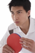 Young man holding table tennis paddle, looking away - blueduck